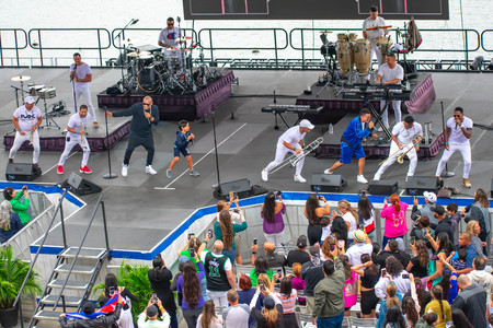 Orlando, Florida. March 17, 2019. Alexander Delgado, his son and Randy Malcom sing and dance with the band by Zone People at Seaworld in International Drive Area. Фото со стока - 121384066