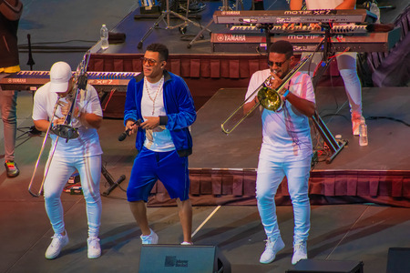 Orlando, Florida. March 17, 2019. Randy Malcom by Zone People dancing with two trumpeters from the band at Seaworld in International Drive Area (1) Редакционное