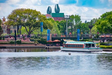 Orlando, Florida. April 02, 2019. Partial view of Disney Swan Hotel and taxi boat sailing on lake at Epcot in Walt Disney World. Редакционное