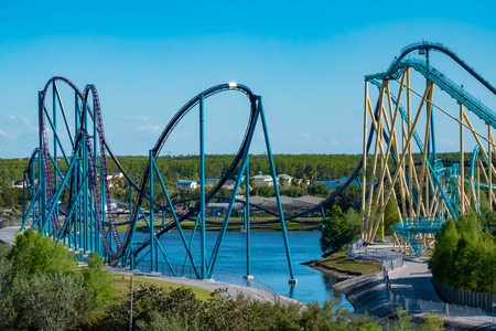 Orlando, Florida. April 20, 2019. Aerial view of Mako and Kraken rollercoasters on lightblue sky background at Seaworld in International Drive area. Фото со стока - 122360753