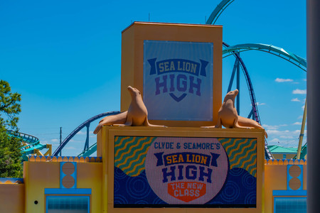 Orlando, Florida. April 20, 2019. Sea Lion High The New Class show sign and Kraken rollercoaster on lightblue sky background at Seaworld. Фото со стока - 122360761