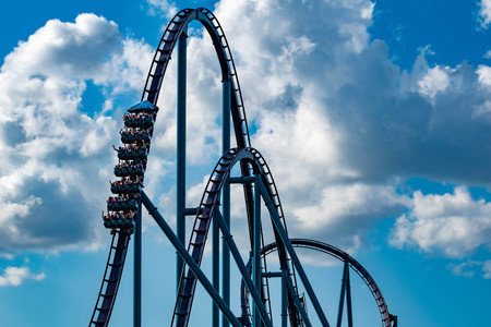 Orlando, Florida. April 26, 2019. People having fun amazing Mako rollercoaster on lightblue cloudy sky background at Seaworld Фото со стока - 122360847