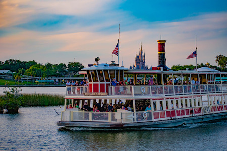 Orlando, Florida. April 23, 2019. Partial view of Cinderella's Castle and Disney Ferry boat on colorful sunset bakcground at Walt Disney World area Фото со стока - 122360853