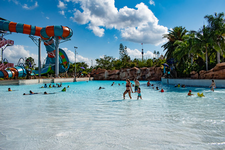 Orlando, Florida. April 26, 2019. People enjoying wave pool and partial view of Karekare curl on lightblue sky cloudy background at Aquatica Фото со стока - 122360857