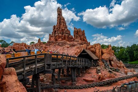 Orlando, Florida. May 10, 2019. People having fun Big Thunder Mountain railroad on cloudy sky background in Magic Kingdom at Walt Disney World (1)