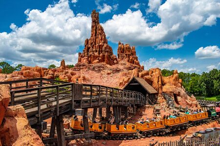 Orlando, Florida. May 10, 2019. People having fun Big Thunder Mountain railroad on cloudy sky background in Magic Kingdom at Walt Disney World (6) Редакционное