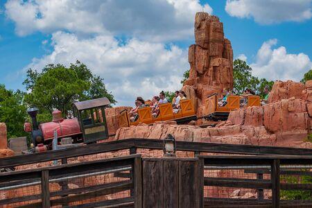 Orlando, Florida. May 10, 2019. People having fun Big Thunder Mountain railroad on cloudy sky background in Magic Kingdom at Walt Disney World (8)