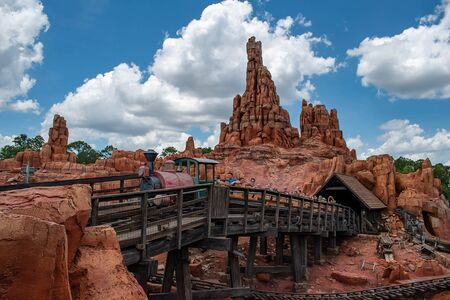 Orlando, Florida. May 10, 2019. People having fun Big Thunder Mountain railroad on cloudy sky background in Magic Kingdom at Walt Disney World (9)