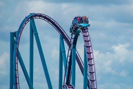 Orlando, Florida. June 30, 2019. Terrific view of people having fun Mako roller coaster on lightblue sky cloudy background at Seaworld 13 Редакционное