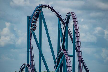 Orlando, Florida. June 30, 2019. Terrific view of people having fun Mako roller coaster on lightblue sky cloudy background at Seaworld 14 Редакционное