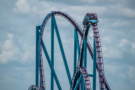 Orlando, Florida. June 30, 2019. Terrific view of people having fun Mako roller coaster on lightblue sky cloudy background at Seaworld 15 Редакционное