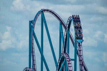 Orlando, Florida. June 30, 2019. Terrific view of people having fun Mako roller coaster on lightblue sky cloudy background at Seaworld.