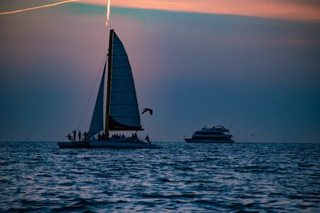 Clearwater Beach, Florida. June 24, 2019. People enjoying sailboat and luxury yacht on colorful sunset background in Gulf Coast Beaches 1 Editorial