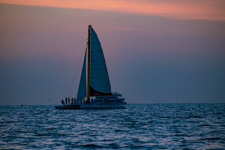Clearwater Beach, Florida. June 24, 2019. People enjoying sailboat and parasail on colorful sunset background in Gulf Coast Beaches 2