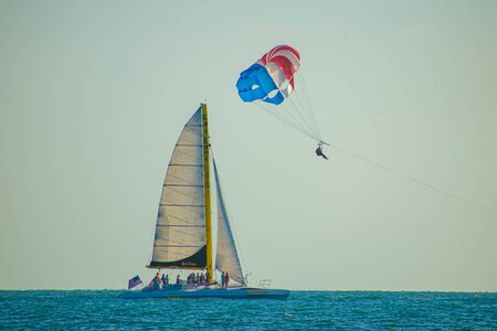 Clearwater Beach, Florida. June 24, 2019. People enjoying sailboat and parasail on colorful sunset background in Gulf Coast Beaches 3
