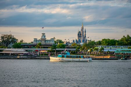 Orlando, Florida. June 03, 2019. Taxi boat and panoramic view of Cinderellas Castle and vintage Train Station at Magic Kingdom in Walt Disney World.