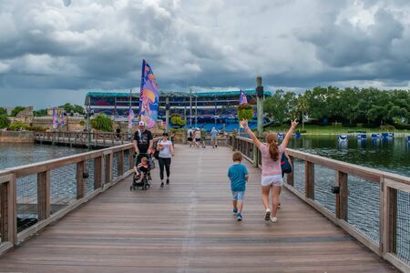 Orlando, Florida. June 17, 2019. Nice girl raising her arms while walking with her family at Seaworld.