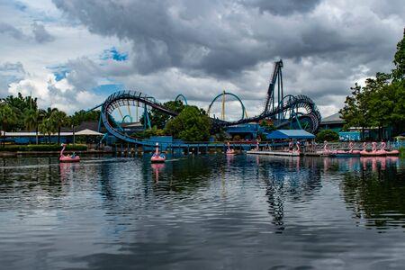 Orlando, Florida. June 17, 2019. Panoramic view of Mako rollercoaster and swan paddle boats at Seaworld. Редакционное
