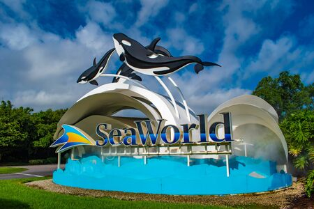 Orlando, Florida. June 17, 2019. Seaworld sign and whale figures on lightblue cloudy background 1