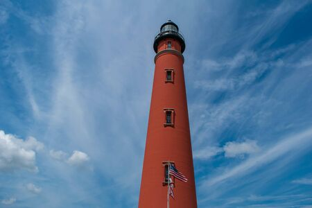 Ponce de Leon Inlet, Florida. July 19, 2019 Partial view of historic lighthouse on lightblue sky background. 2
