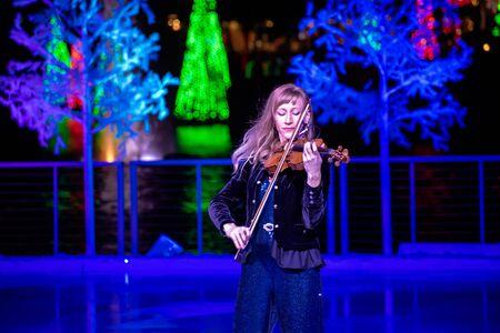 Orlando, Florida . November 24, 2019. Woman violinist playing holiday music on Seaworlds Christmas Celebration (1)