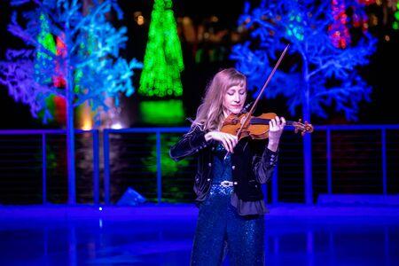 Orlando, Florida . November 24, 2019. Woman violinist playing holiday music on Seaworlds Christmas Celebration (4) 報道画像