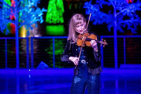 Orlando, Florida . November 24, 2019. Woman violinist playing holiday music on Seaworlds Christmas Celebration (6)