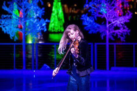 Orlando, Florida . November 24, 2019. Woman violinist playing holiday music on Seaworlds Christmas Celebration (8)