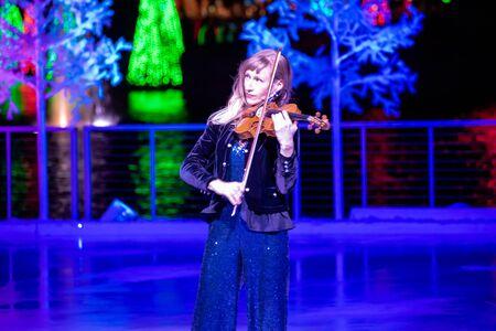 Orlando, Florida . November 24, 2019. Woman violinist playing holiday music on Seaworlds Christmas Celebration (10)