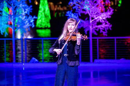 Orlando, Florida . November 24, 2019. Woman violinist playing holiday music on Seaworlds Christmas Celebration (12) 報道画像