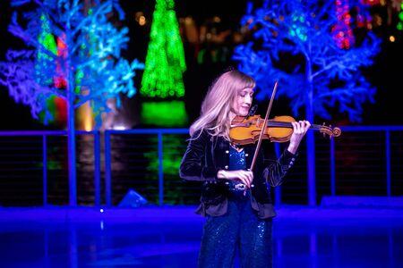 Orlando, Florida . November 24, 2019. Woman violinist playing holiday music on Seaworlds Christmas Celebration (5) 報道画像