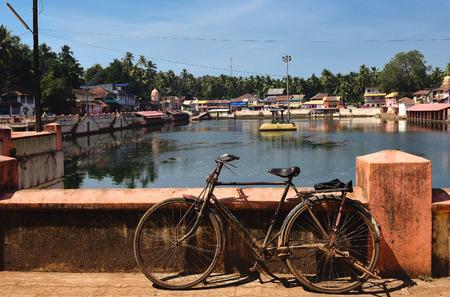 pilgrim journey: View to the sacred lake Kotiteerkha in Gorarna, Karnataka, India. Old bicycle is standing near lake railing