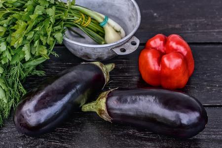 Set of fresh vegetables on dark wood table background: pepper, greens, eggplants. Still life photography.