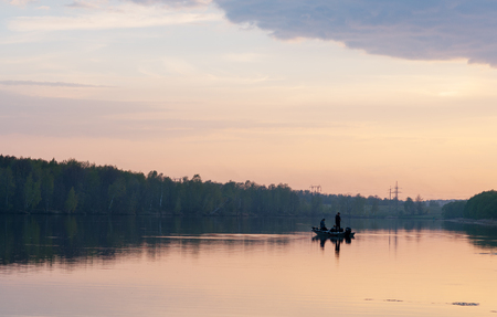 Deux pêcheurs au bateau au coucher du soleil Banque d'images - 76837665