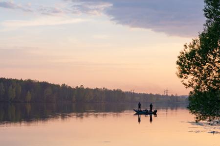 Deux pêcheurs au bateau au coucher du soleil Banque d'images - 76570756