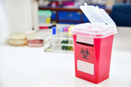Disposal container; reducing medical waste disposal. Small Medical Waste sharps container with sharps for biohazand. Foto de archivo