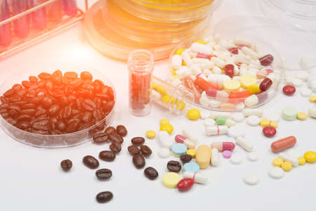 Pharmaceutical medicament, cure in container for health and fresh roasted coffee beans in plate. Archivio Fotografico