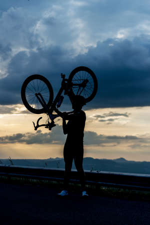 Silhouette a man in action lifting bicycle above his head.