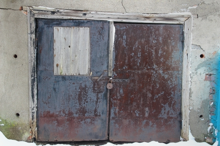 old closed gate of garage in the brick plastered wall photo