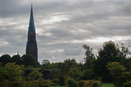 well maintained: in foreground is well maintained Park, in the background the cathedral with clock against the grey sky