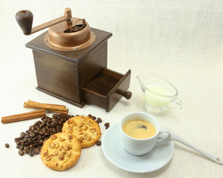 coffeebeans: Coffee cup, biscuit grinder and coffeebeans on table.