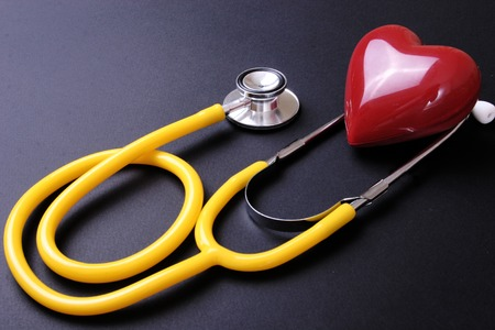 prescription pad: Stethoscope and red heart isolated on black white background. Stock Photo