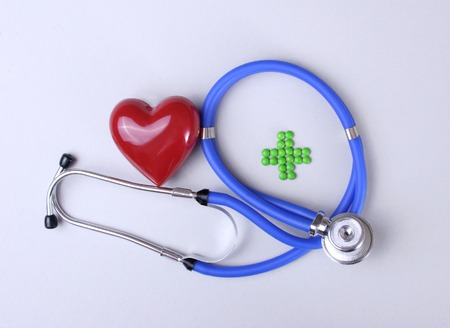 Green medical cross sign stethoscope red heart.