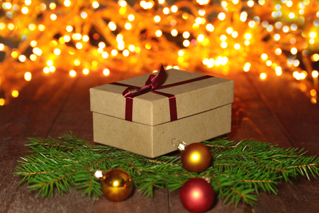 Cristmas: Christmas Composition with Gift box and light, red balls on wooden table. Stock Photo