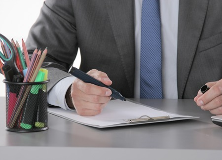 mobilephone: portrait of business man hand writing at notebook and holding mobilephone.