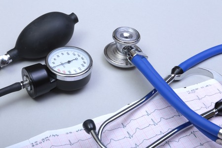 Stethoscope head and silver pen lying on cardiogram on clipboard pad. Cardio therapeutist assistance, physician make cardiac physical, pulse beat measure document, arrhythmia idea, pacemaker concept. Stock Photo
