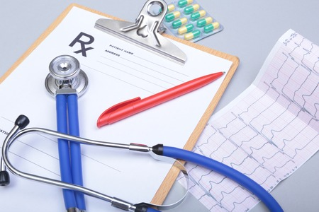 myocardium: Stethoscope head and silver pen lying on cardiogram on clipboard pad. Cardio therapeutist assistance, physician make cardiac physical, pulse beat measure document, arrhythmia idea, pacemaker concept. Stock Photo