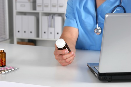 Close-up view of female doctor hand holding bottle with pills and writing prescription. Healthcare, medical and pharmacy concept.
