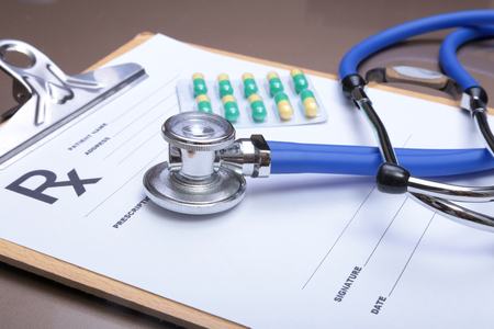prophylaxis: Stethoscope head and silver pen lying on cardiogram on clipboard pad. Cardio therapeutist assistance, physician make cardiac physical, pulse beat measure document, arrhythmia idea, pacemaker concept. Stock Photo