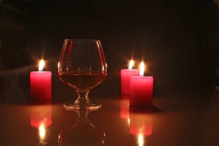 snifter: Glass of brandy or cognac and candle on the wooden table. Stock Photo